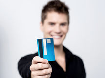 Take my credit card for shopping!. Young male showing his credit card to camera Stock Images