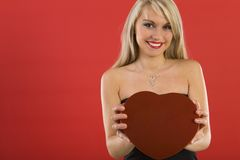 Take my heart. Beautiful woman in black dress, holding heart-shaped box of chocolates. Smiling and looking at camera. Front view Stock Photo