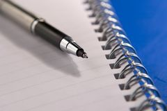 Take note. Notebook and pen on blue background, focus on pen nib Royalty Free Stock Photos