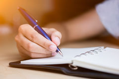 Taking note on notebook by blue ball pen. royalty free stock photography