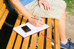 Take notes on a bench in a diary. In nature sitting and doing things you love Royalty Free Stock Photo