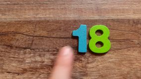 Take the number 2018 from colored wooden figurines from a wooden table with your finger stock footage