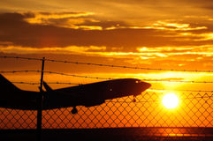 Take Off. Silhouette of a commercial plane taking off behind a security fence at Denver international airport Royalty Free Stock Images