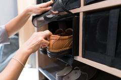Take off brown man shoes in the shoe rack for use. Female open net and ake off brown man shoes in the shoe rack for use, they are arrange and neatly and close royalty free stock photos