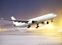 Take-off in non-flying weather. Airport and white plane taking off at non-flying weather, snowstorm Stock Photos