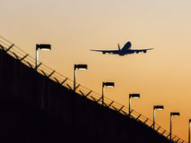 Take-off of the plane at sunset. Plane silhouette in the sky at take-off at sunset Royalty Free Stock Photography