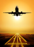 Take-off runway. Passenger plane fly up over take-off runway from airport at sunset Royalty Free Stock Photo