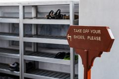 Take off your shoes please. sign in english language. Before entering temple Stock Image