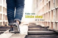 Take One Little Step. At a Time  - inspiration quote on concept photo, woman walking on the wood bridge Stock Photography