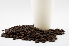Take-out coffee cup on coffee beans. stock images