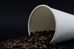Take-out coffee cup with spilled coffee beans, black background. Coffee beans stock photo