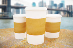 Take out coffee cups. Disposable white paper coffee cups with blank brown labels on wooden table. Modern city background. Mock up, 3D Rendering Royalty Free Stock Photography