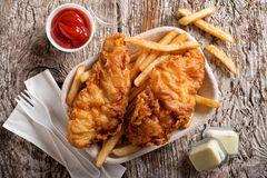 Take Out Fish and Chips. Delicious fish and chips in a take out container with ketchup, tartar sauce, paper napkins and a plastic fork on a rustic wood table top royalty free stock photography