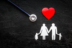 Take out health insurance for family. Stethoscope, paper heart and silhouette of family on black background top view.  Royalty Free Stock Photos