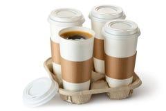 Take-out kaffe fyra i hållare. En kopp öppnas. Royaltyfria Foton