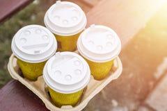 Take-out kaffe fyra i hållare Ta kaffe för att arbeta för det hela kontoret KaffeTid begrepp royaltyfri foto