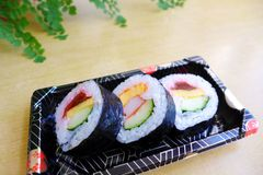 Take out sushi snack platter. A photograph showing some delicious sushi pieces on a take away platter box.  Packed for snacks to go.  Ingredients include Stock Image