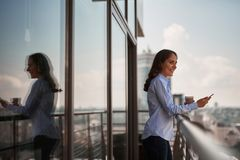 Young office woman enjoying city view on balcony stock photography