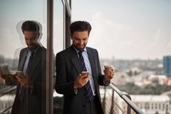 Man in office suit checking massages on phone stock image