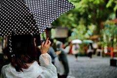 Take photo the activities merit of her friends in rain. Stock Photo