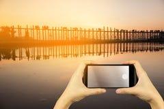 Take photo with smartphone. U Bein Bridge at sunset. Amarapura, Stock Photos