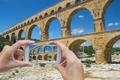 Take a picture of Pont du Gard. In the bottom left of the photo are hands holding some smart phone, whose screen contains photo of Pont du Gard. Background of Royalty Free Stock Image