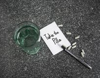 Take the pills text on paper note with medicines and glass of water. On table Stock Images