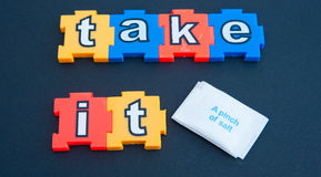 Take it with a pinch of salt. 'Take it ' in jigsaw type colorful lower case letters  with a white packet marked ' A pinch of salt ' on a dark background Royalty Free Stock Images