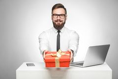 Take present! Portrait of happy young boss in in white shirt and black tie are sitting in office and giving you a red box, royalty free stock image