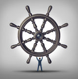 Take The Reins. And change course business concept as a businessman holding a ship wheel steering gear as a symbol and financial metaphor for taking control and Stock Photo