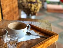 Take a rest with Coffee cup in cafe. White coffee cup, spoon and glass in wooden tray on vintage wooden table Royalty Free Stock Image