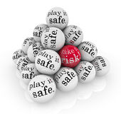 Take a Risk or Play it Safe Pyramid Balls. A pyramid of balls reading Play it Safe and one with the words Take a Risk to illustrate going beyond your comfort Royalty Free Stock Photography