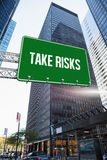 Take risks against skyscraper in city. The word take risks and green billboard sign against skyscraper in city Royalty Free Stock Photo