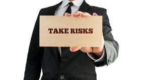 Take risks. Businessman holding a rectangular wooden sign saying Take risks. Over white background Stock Photo
