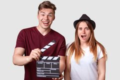 Take and scene. Positive youngster holds clapperboar or film slate, indignant surprised female in headgear opened mouth widely,. Reacts on something surprising stock photography