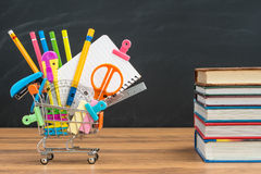 Take school supplies in shopping cart with textbook Stock Photos