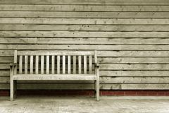 Take a seat. Wooden bench and wall in black and white with the red brick in coloure Royalty Free Stock Image