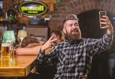 Take selfie photo to remember great evening in pub. Man bearded hipster hold smartphone. Taking selfie concept. Online. Communication. Send selfie to friends stock photography