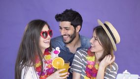 Take selfie video on vacation. Friends taking selfie video with a selfie stick, two pretty long-haired girls in hawaiian wreaths and casual summer t-shirts stock video footage