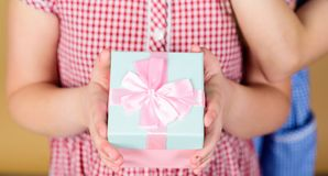 Take this. Share and generosity. Thank you so much. Child hold gift box beige background. Kid girl delighted gift. Girl