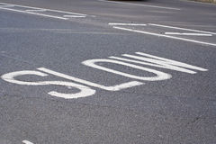 Take it slow. Slow road markings on a British street Royalty Free Stock Images