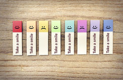 Take smile ads. Colored paper stickers on a wooden background Royalty Free Stock Images