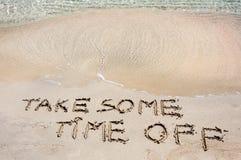 TAKE SOME TIME OFF geschrieben auf Sand auf einem schönen Strand, Blau bewegt in Hintergrund wellenartig lizenzfreie stockbilder