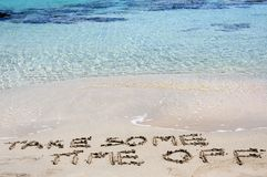 TAKE SOME TIME OFF written on sand on a beautiful beach, blue waves in background. TAKE SOME TIME OFF written on sand on a beautiful beach,  blue waves in Royalty Free Stock Images
