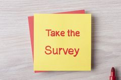 Take the Survey. Handwritten on note. Top view royalty free stock photo