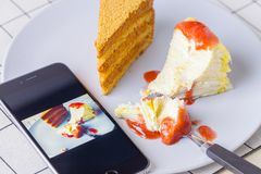 Take a sweet cake with a phone. Modern life in photography. Use mobile phones to record impressive things like food royalty free stock image