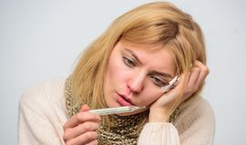 Take temperature and assess symptoms. High temperature concept. Woman feels badly ill sneezing. Girl in scarf hold. Thermometer and tissue close up. Measure stock photography