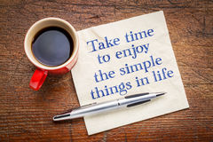 Take time to enjoy the simple things in life. Inspirational handwriting on a napkin with a cup of coffee Stock Photo