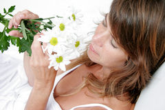Take time to smell the flowers. Woman smelling flowers Stock Image