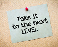 Take it to the next level. Message. Recycled paper note pinned on cork board. Concept Image Stock Photos